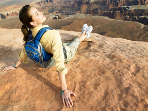 Woman with backpack sitting on cliffの写真素材 [FYI02939841]