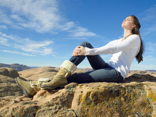 Young woman sitting on rockの写真素材 [FYI02939870]