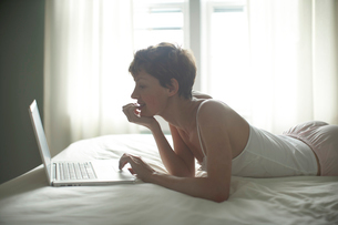 Mid adult woman using laptop on bedの写真素材 [FYI02939888]