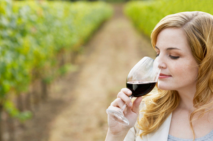Young woman smelling red wineの写真素材 [FYI02939890]