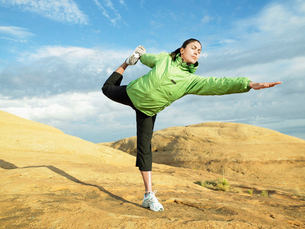 Woman doing yoga on rocky hillの写真素材 [FYI02939891]