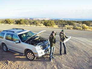 Couple with broken car on roadsideの写真素材 [FYI02939901]