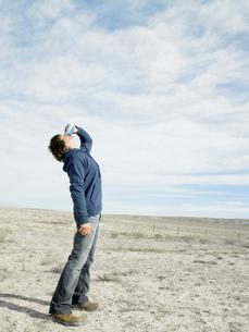 Mid adult man drinking beer in desertの写真素材 [FYI02939907]