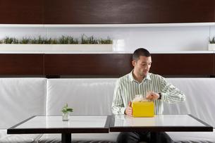 Man with present waiting in restaurantの写真素材 [FYI02939917]