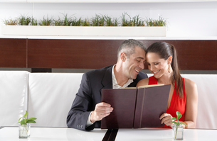 Couple reading menu in restaurantの写真素材 [FYI02939918]