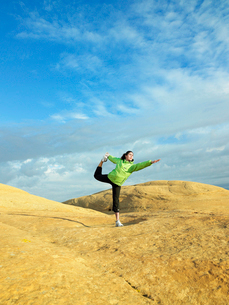 Woman doing yoga on rocky landscapeの写真素材 [FYI02939936]
