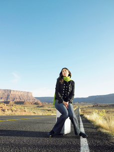 Woman hitchhiking on rural roadの写真素材 [FYI02939945]
