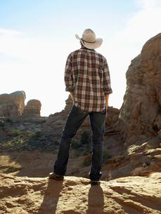 Man in cowboy hat standing on cliffの写真素材 [FYI02939970]