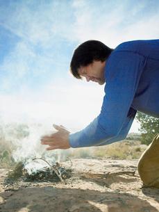 Man lighting fire on rockの写真素材 [FYI02939973]