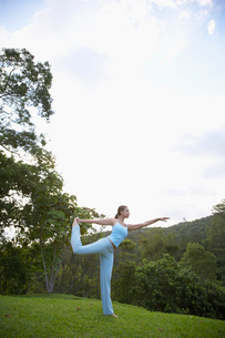 Young woman doing yoga in parkの写真素材 [FYI02939991]