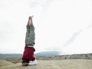 Man standing on head at rock strataの写真素材 [FYI02940033]