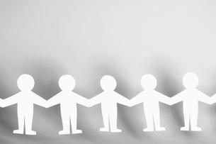 Row of white paper figurinesの写真素材 [FYI02940035]