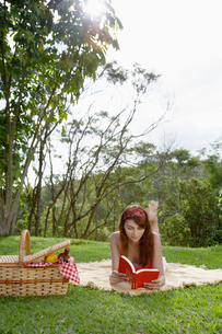 Young woman reading book at picnicの写真素材 [FYI02940056]
