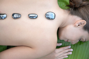 Young woman receiving hot stone therapyの写真素材 [FYI02940059]