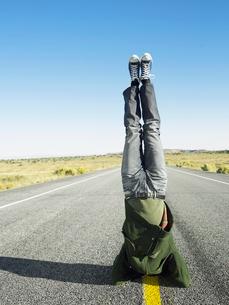 Man standing on head on roadの写真素材 [FYI02940082]