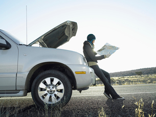 Woman with broken car holding road mapの写真素材 [FYI02940091]