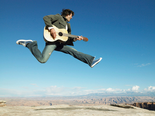 Man jumping and playing acoustic guitarの写真素材 [FYI02940096]