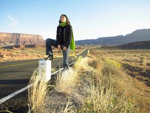 Woman hitchhiking on rural roadの写真素材 [FYI02940097]