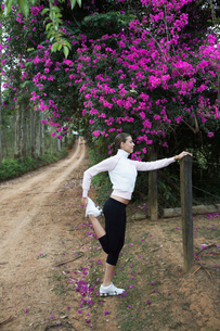 Young woman stretching on dirt roadの写真素材 [FYI02940105]