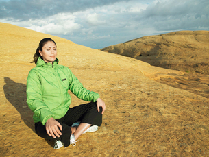 Woman meditating on rocky hillの写真素材 [FYI02940111]