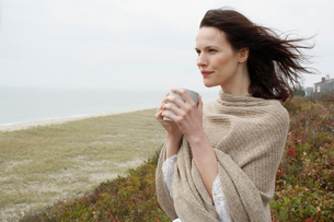 Young woman drinking coffee at beachの写真素材 [FYI02940116]