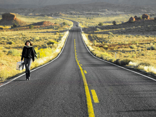 Woman walking on empty highwayの写真素材 [FYI02940135]