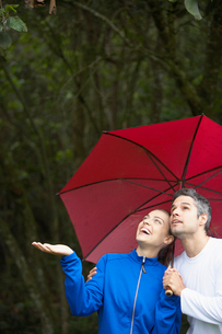 Couple looking at rain under umbrellaの写真素材 [FYI02940157]