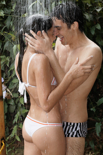 Young couple hugging under showerの写真素材 [FYI02940179]