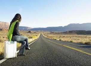 Woman hitchhiking on rural roadの写真素材 [FYI02940189]