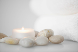 Towels beside candle and stonesの写真素材 [FYI02940190]