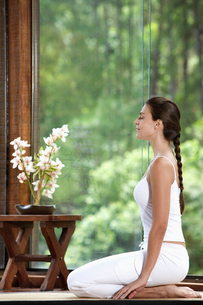 Woman meditating on floor near windowの写真素材 [FYI02940194]