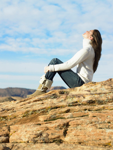 Young woman sitting on rocky hillの写真素材 [FYI02940222]