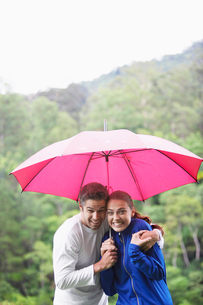 Couple hugging under umbrellaの写真素材 [FYI02940236]