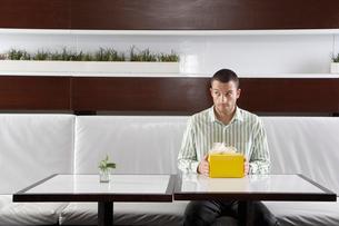 Man with present waiting in restaurantの写真素材 [FYI02940253]