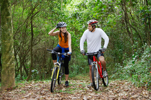 Couple cycling in forestの写真素材 [FYI02940258]