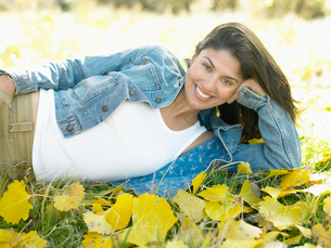 Woman lying on autumnal leavesの写真素材 [FYI02940264]