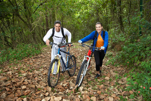 Couple with mountain bikes in forestの写真素材 [FYI02940327]
