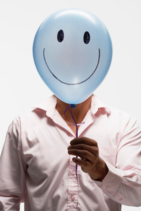 Man holding balloon with smiley faceの写真素材 [FYI02940338]