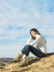 Young woman sitting on rocky hillの写真素材 [FYI02940357]