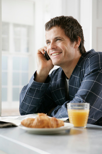 Man on the phone at breakfast tableの写真素材 [FYI02940361]