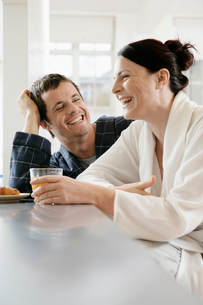 Couple laughing at breakfast tableの写真素材 [FYI02940478]