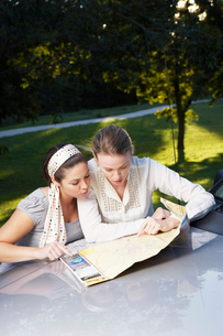 Two women reading road map on carの写真素材 [FYI02940482]