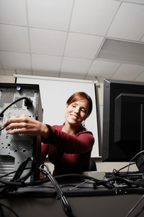 student adjusting computer cableの写真素材 [FYI02940502]