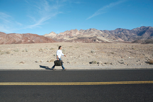 Man with suitcase walking on highwayの写真素材 [FYI02940516]