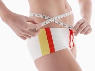 Young woman measuring waistの写真素材 [FYI02940528]