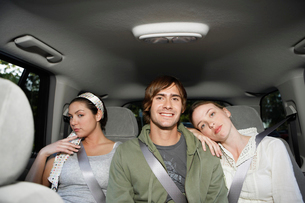 man sitting with two women on back seatの写真素材 [FYI02940561]