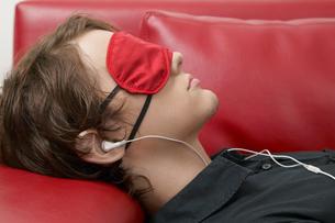 Man with sleep mask listening to musicの写真素材 [FYI02940583]