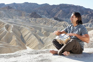 Man playing drums in desertの写真素材 [FYI02940607]