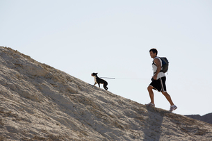 Man with dog hiking on hillの写真素材 [FYI02940608]