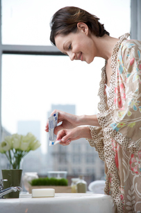 Woman squeezing toothpaste out of tubeの写真素材 [FYI02940690]